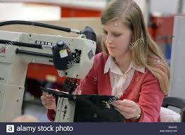 female sewing machine worker in a leather handbag factory stock