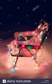 decorated lawn chair with lit christmas lights covered in snow