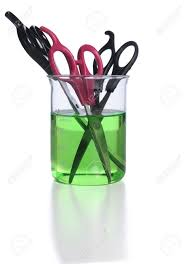 hair cutting scissors in a beaker of green disinfectant stock