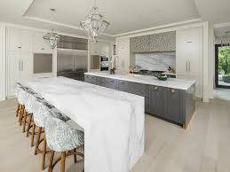 contemporary kitchen islands with seating calcutta marble waterfall kitchen island with blond wood floors
