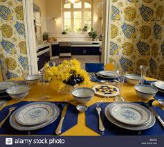 wallpaper in dining room blue napkins and crockery on yellow tablecloth in diningroom with