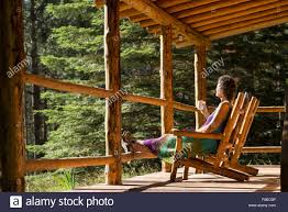 woman enjoying a drink on the porch of a log cabin at the