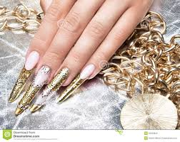 beautiful long nails in a gold design with stock photo image