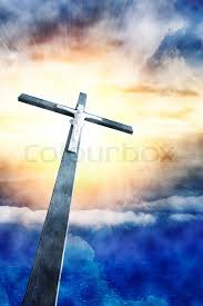 cross in sunrays against cloudy sky stock photo colourbox