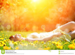 young beautiful woman lying on grass full of spring flowers