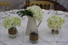 wedding flowers jam jars country garden wedding table centre with jug and jam jars with
