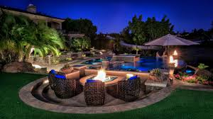 natural swimming pool design with a fire pit and outdoor seating