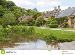 old english stone cottages by a river in countryside stock photo
