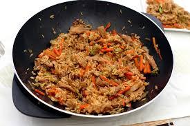 cuisiner avec un wok wok de porc riz carottes brocolis et sauce soja et sésame