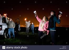 people looking for stars and aliens in the night sky using torches