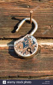 old rusted lock hanging on a nail on a wooden wall stock photo