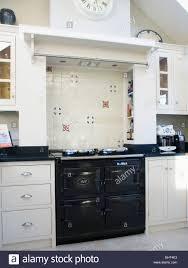 black aga oven below tiled splash back in modern white kitchen