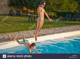 two girls teenager pool country style dive italy house summertime
