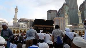 sitting in front of the kaaba with the abraj al bait in the