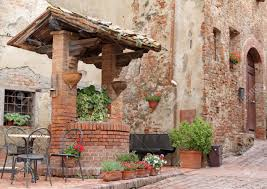 brick old well decorated with plants and flowers on italian street