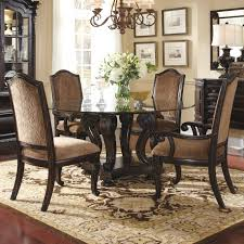 round black glass dining table with carved brown wooden legs plus