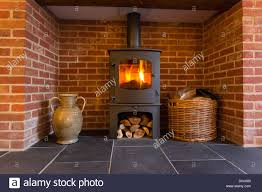 Wood Burning Fireplace by Fire In Wood Burning Stove In Brick Fireplace With Basket Of Cut