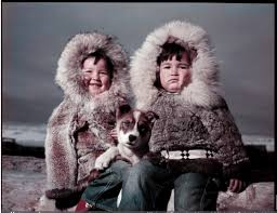 two young inuit boys with their dog on a beach in alaska circa