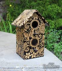 wooden birdhouse intricately decorated using butterfly and henna