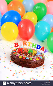 happy birthday chocolate cake with candles and balloons stock