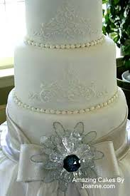 very elegant three tier white wedding cake with silver bows and