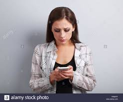 worried unhappy young woman typing sms and looking on mobile phone