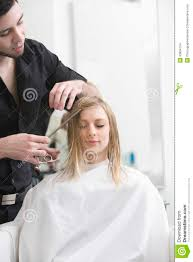 woman getting haircut from hairdresser at salon stock images