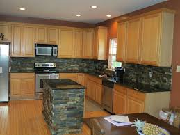 maple cabinets with black island gray and brown rectangle back splash tile plus light brown wooden