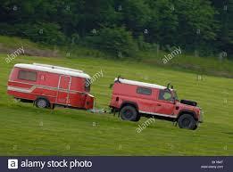 red land rover defender red land rover defender 110 hard top towing a matching red caravan