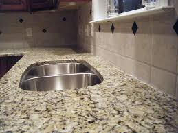 granite countertop dark cabinets with light floors sink pipes