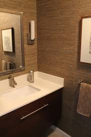powder room with grasscloth wallpaper walnut stained cabinetry