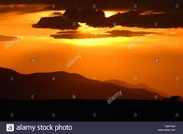 a soft orange sunset along a line of colorado foothills stock
