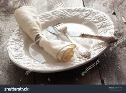 Informal Table Setting by White Rose Patterned Dinner Plate With Silverware And A Napkin In