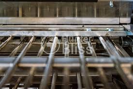 Book Paper Folding - paper folding machine fold unit inside metal bars press closeup