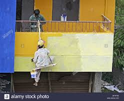 a painter a painter is seating on a cradle and working on a building s