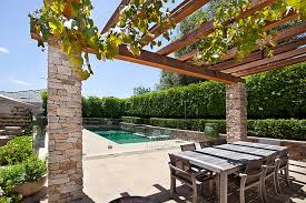 Grape Vine Pergola by Pergola With Alpine Stone Clad Pillars And Chunky Timber Beams Is