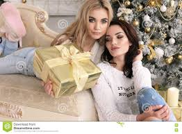 beautiful girls in cozy home clothes celebrating new year holida