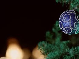 blue ornament hanging on a tree wtih black background