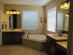 bathroom corner jacuzzi tub with two windows glass door shower corner jacuzzi tub with two horizontal blinds two bathroom vanities under frameless mirrors and wallsconces