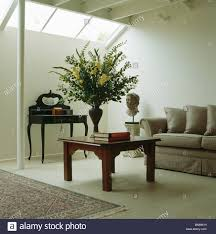 Modern Beige Sofa by Large Flower Arrangement On Wooden Coffee Table And Beige Sofa In