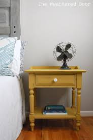 a mustard yellow nightstand with a milk glass knob the weathered