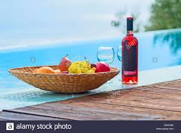 Bowl Of Fruits Healthy Bowl Of Fruits And Bottle Of Wine In Poolside Stock Photo