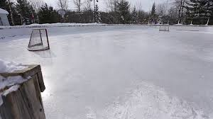 outdoor hockey rink with snowy forest background upward tilt