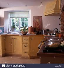 white blind on window above sink in country kitchen with yellow