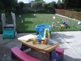kids backyard ideas with boys playing water and splash pad outdoor