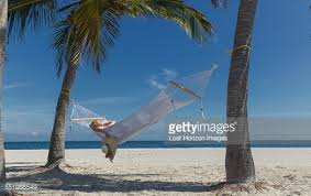 young woman reclining on hammock between palm trees on miami beach
