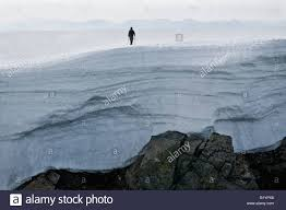Large Cornice Silhouette Of Hiker Above Large Snow Cornice At Summit Of Ben