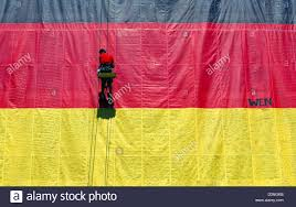 a man ropes down a 300 square metres german flag in berlin