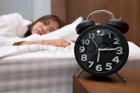asian woman sleeping in bed and alarm clock stock photo colourbox