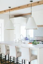 white and blue kitchen with white leather stools with brass